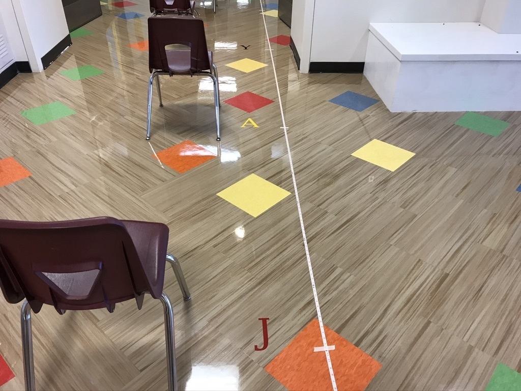 Teachers and custodians working together putting 6 ft social distance points on the floor at JES.